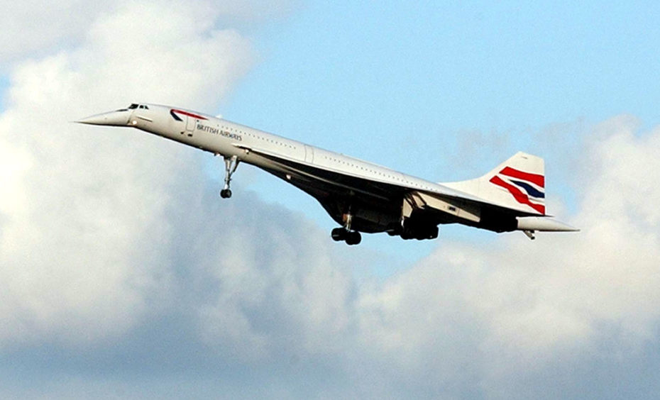 Spectators watch as the first of three Concorde jets approach Heathrow Airport on their last ever flight