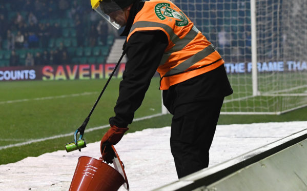 A flare is doused  at Hibs-Celtic cup tie last month