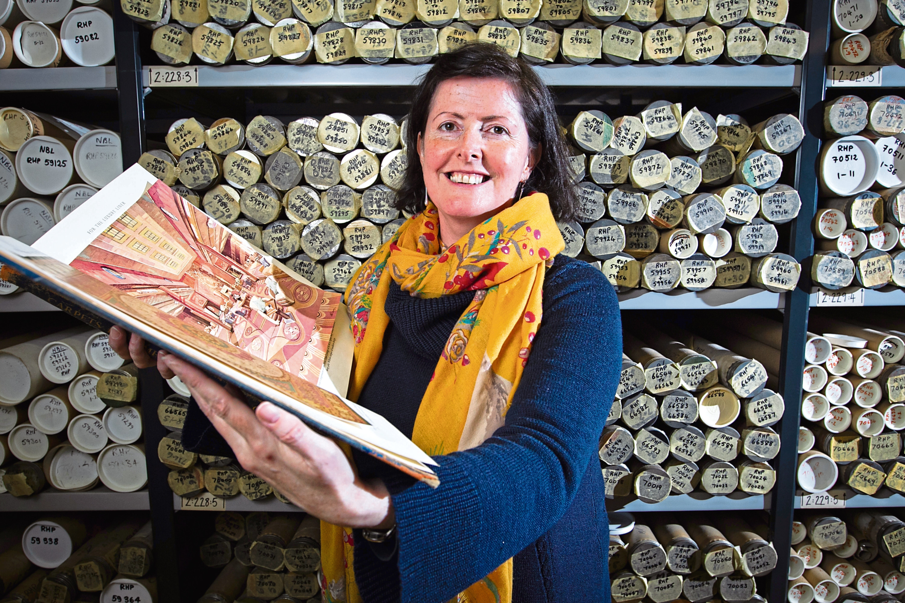 Glasgow University archivist, Claire McDade, with some of the carpet and textile designs in the university's archives, as they are due to launch a new exhibition, showing how Glasgow's carpet factories made carpets for all over the world.