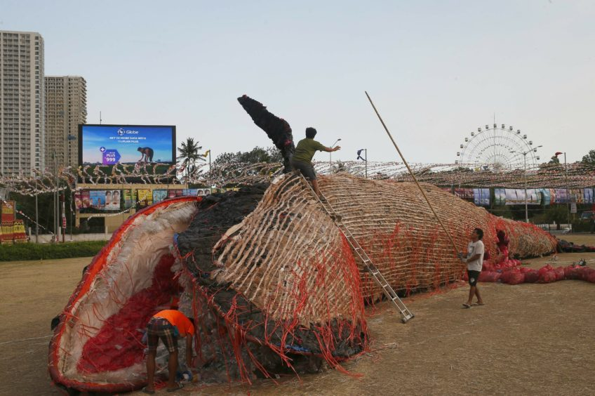 Workers put finishing touches on an installation art of a beached blue whale with its intestines full of plastics to depict the plastics pollution of the world's oceans in Manila, Philippines