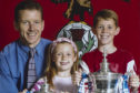 Ryan Christie was keen to get his hands on silverware from an early age,  pictured here with his dad and sister, Paige, in 2004