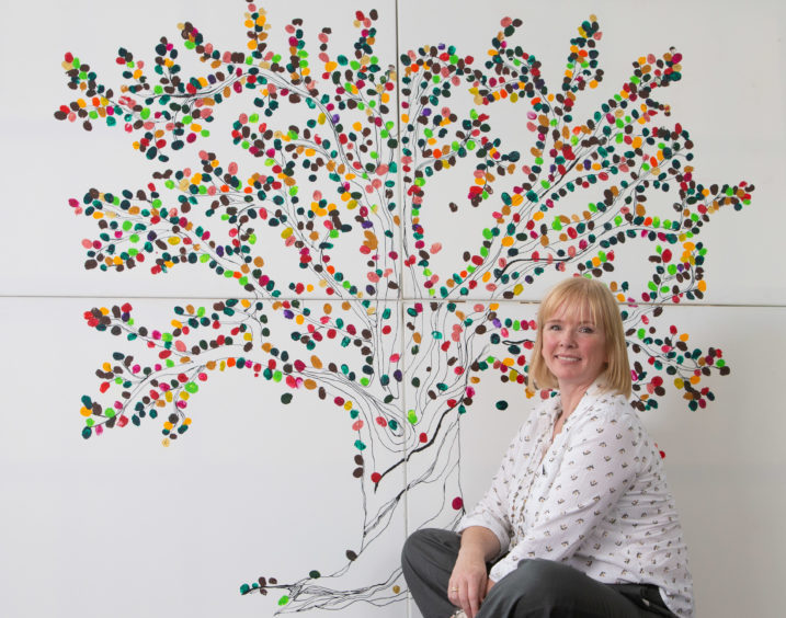 Student Heather Gilchrist unveils the Tree of Life artwork at the University of the West of Scotland's Lanarkshire campus for International Day of the Midwife