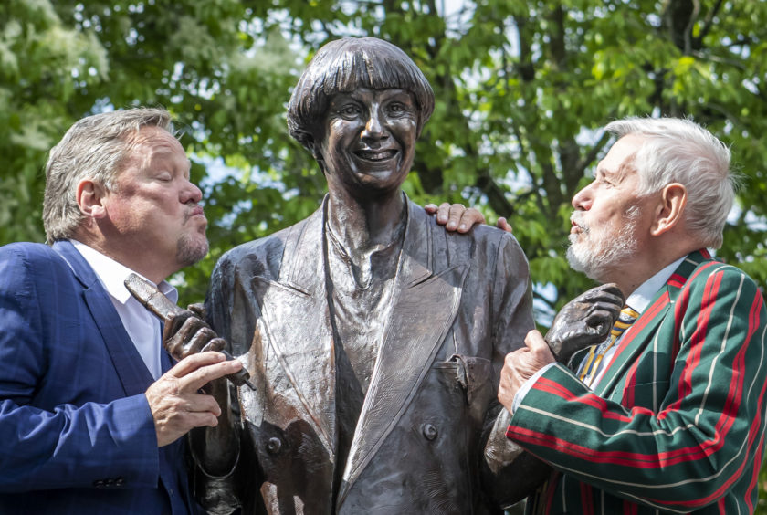 A statue of the late comedian Victoria Wood is unveiled in her hometown,  Bury, by comedian Ted Robbins, left, and her brother Chris Foote Wood
