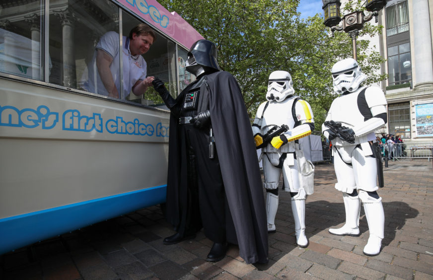 Cosplayers from a galaxy far, far away stop for an ice cream as they celebrate Star Wars Day at Portsmouth Comic Con, held at the city's Guildhall, yesterday