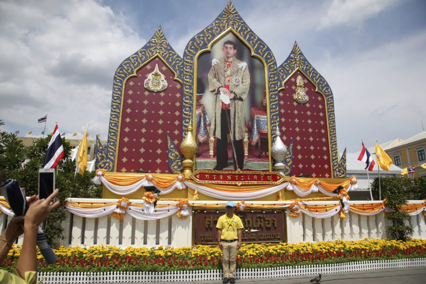 A tourist poses in front of a portrait of King Maha Vajiralongkorn outside the  Grand Palace in Bangkok, Thailand yesterday as the royal coronation begins