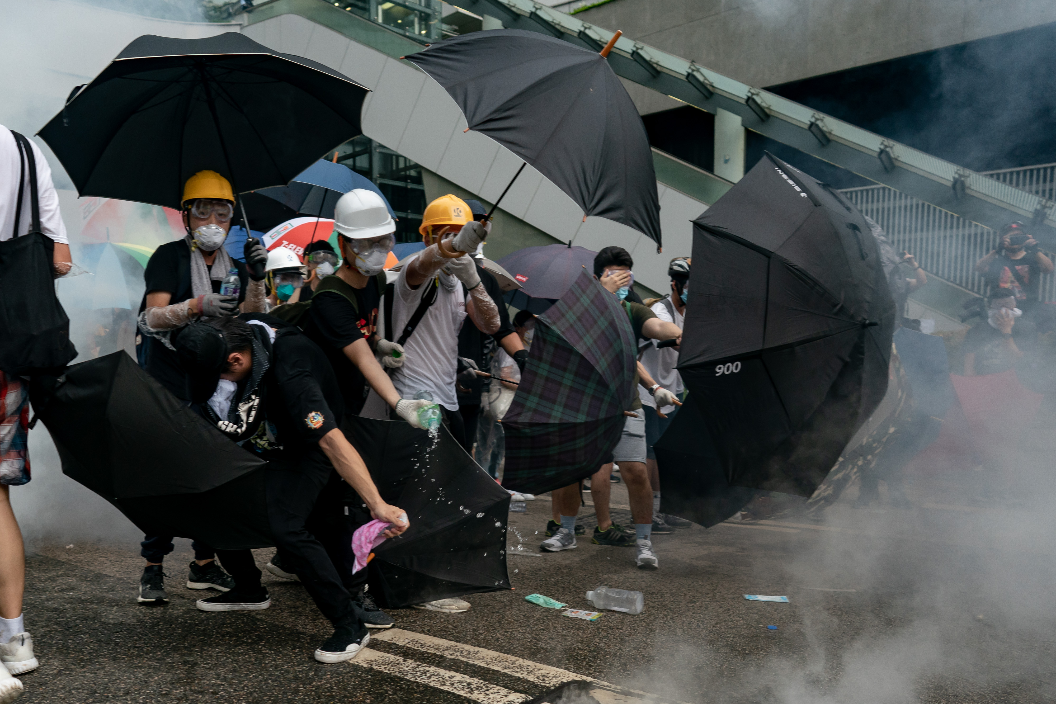 Hong Kong protesters wield umbrellas                as security forces fire pepper spray last week