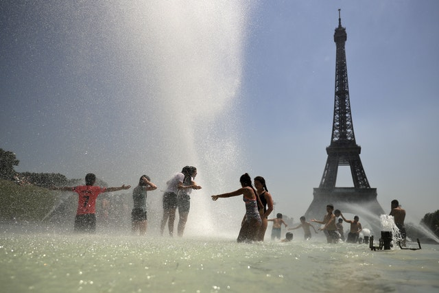 Youngsters cool off at the Trocadero public fountain in Paris