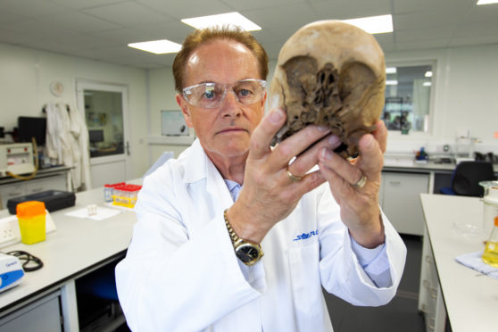 Professor Gordon Cooke, who is a Forensic Anthropologist, who has solved crimes through examining bones. Pic shows him holding a skull which the lab has done tests on. Location Scottish Universities Environmental Research Centre, East Kilbride.