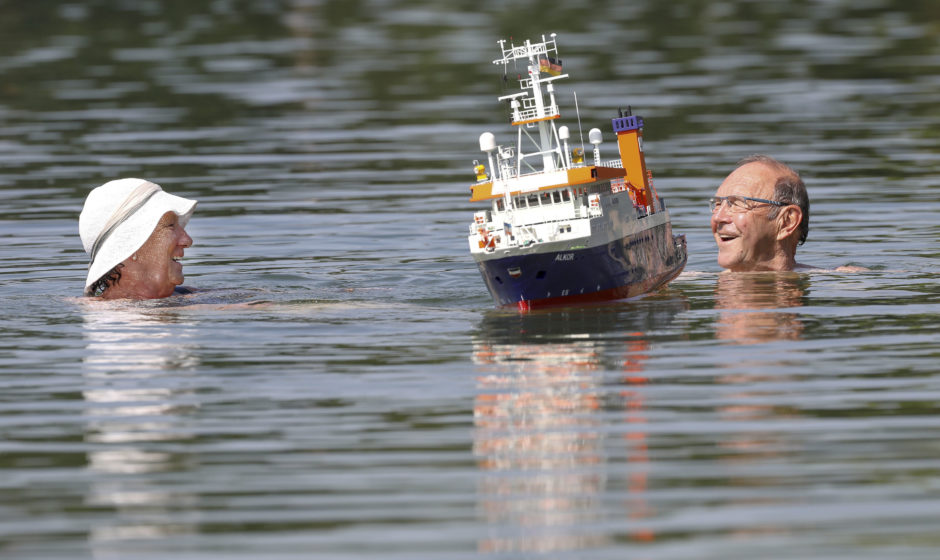 A couple swims beside a model boat in a lake in Ertingen, German