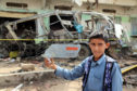 A child displays a part of a missile that hit a bus killing dozens of children in Yemen August last year