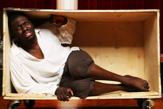 Paul G, playing the title role in 'Henry Box Brown,' enacts the moment he felt his neck break while being transported in a mailed box to escape slavery.