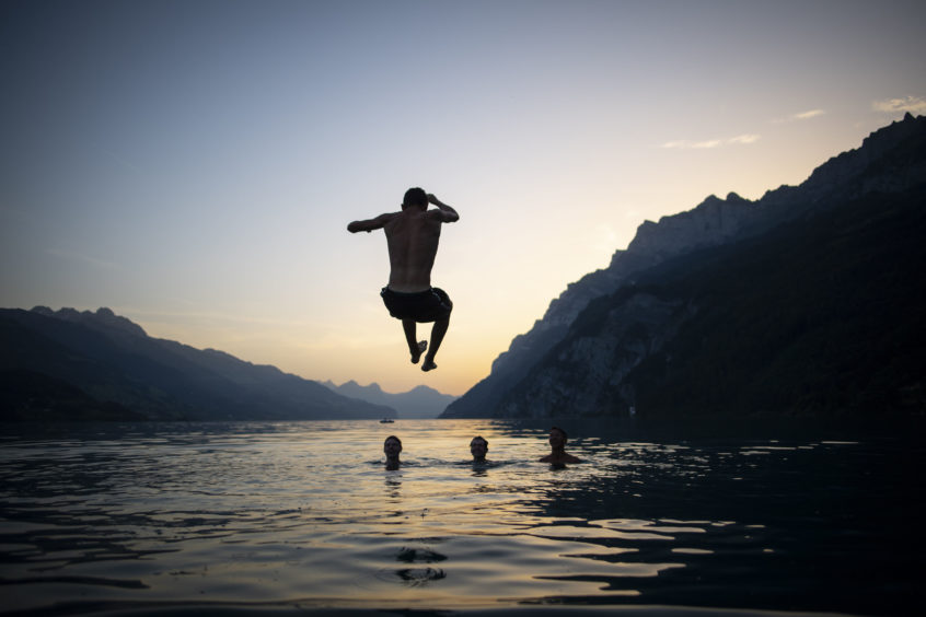 Young people enjoy the evening on Lake Walensee in Walenstadt, Switzerland