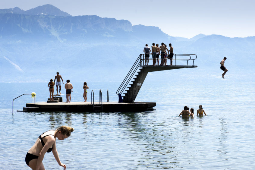 Children jump into the water of Lake Geneva  to cool off