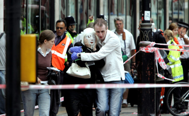 Survivors run to safety after bombs go off                         on the subway and a bus in London on July 7, 2005