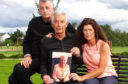 Mark Baxter, his sister Audrey and his dad Chic hold a picture of Eileen