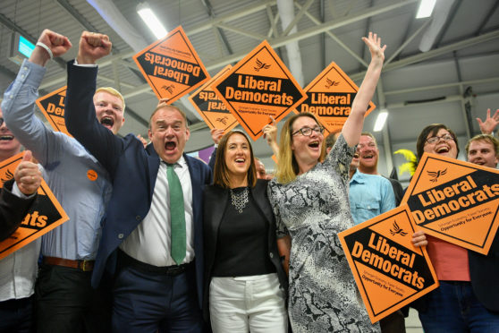 Liberal Democrat MP Jane Dodds, centre, celebrates with supporters as she wins the seat