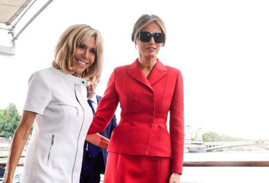 US First Lady Melania Trump (R) and French president's wife Brigitte Macron leave after a boat trip down the River Seine in Paris.