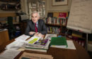 Shadow chancellor John McDonnell in his Westminster office and, behind him, the flipchart detailing Labour's route to government