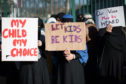 Parents and children holding up signs, as more than half of British adults support primary schools teaching LGBT-inclusive lessons, new research has found.