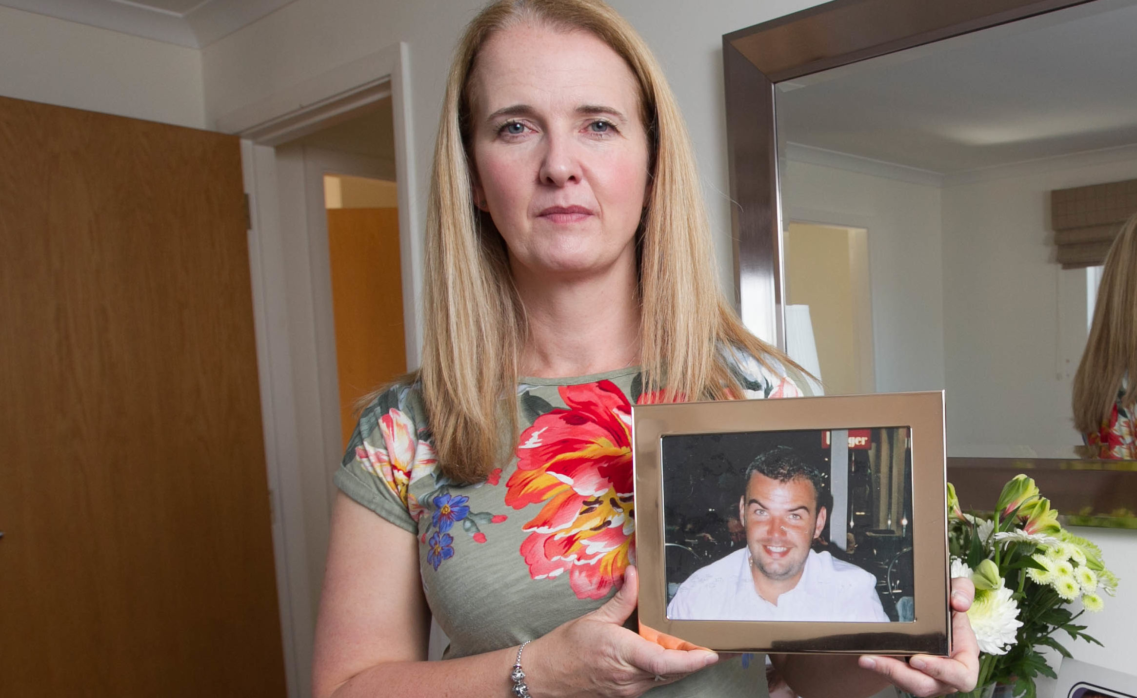 Louise Taggart at home in Edinburgh holding photo of brother Michael Adamson