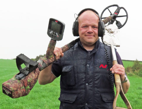 Derek McLennan with his metal detector in a field in Ayrshire