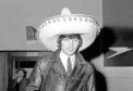 Manchester United footballer George Best wearing a Souvenir Sombrero on his return to London airport following United's defeat of Benfica 5-1 in the second leg of the European Cup quarter final football match. Best scored United's first two goals.