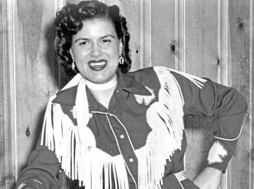 CIRCA 1958:  Country musician Patsy Cline plays the piano wearing a fringed dress and holding a cowboy hat in circa 1958.