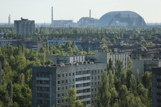The former Chernobyl nuclear power plant, including destroyed reactor four (C), as well as the New Safe Confinement structure (R) that will one day enclose the remains of reactor four, stand behind the abandoned city of Pripyat.