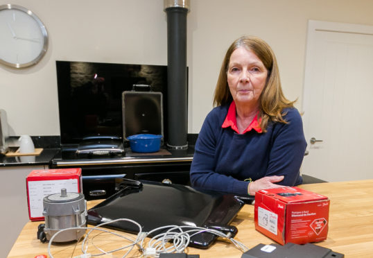 Ruth Patience in her Highland home with some of the spare parts and cabling from heating system