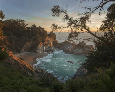 The sun sets over McWay Falls in Big Sur, Monterey, California.