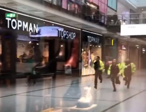Police running through the Arndale Centre in Manchester in response to the incident