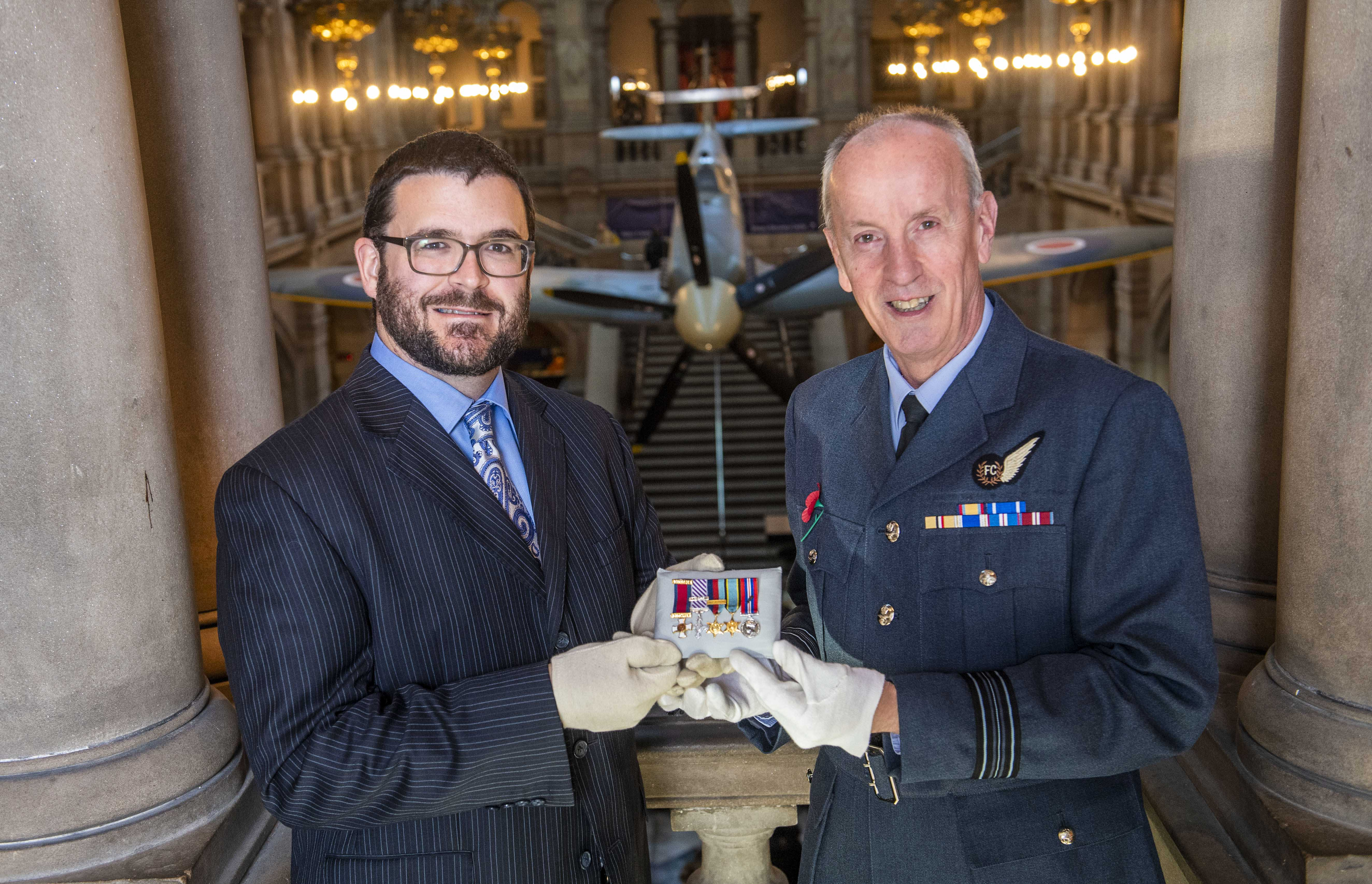 Glasgow Museums curator John Messner (L) and Squadron Leader  Archie McCallum of the 602 City of Glasgow Squadron unveil the new display