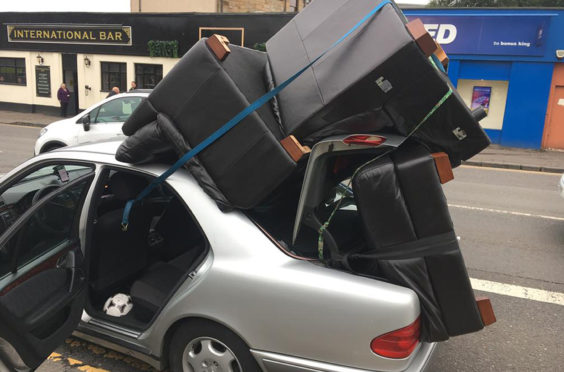 A car caught driving along a city road with a sofa and armchairs piled on the roof