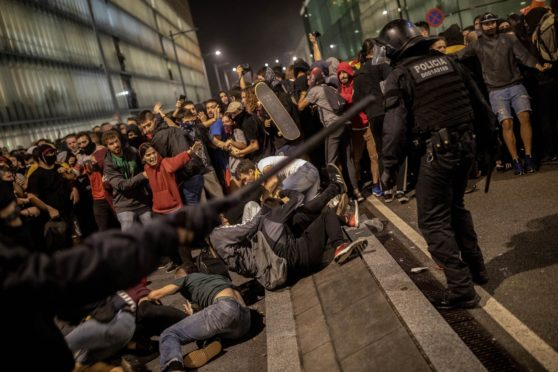 Police clash with protesters during a demonstration at El Prat airport, outskirts of Barcelona, Spain, Monday, Oct. 14, 2019. Spain's Supreme Court on Monday sentenced 12 prominent former Catalan politicians and activists to lengthly prison terms for their roles in a 2017 bid to gain Catalonia's independence, sparking protests across the wealthy Spanish region.