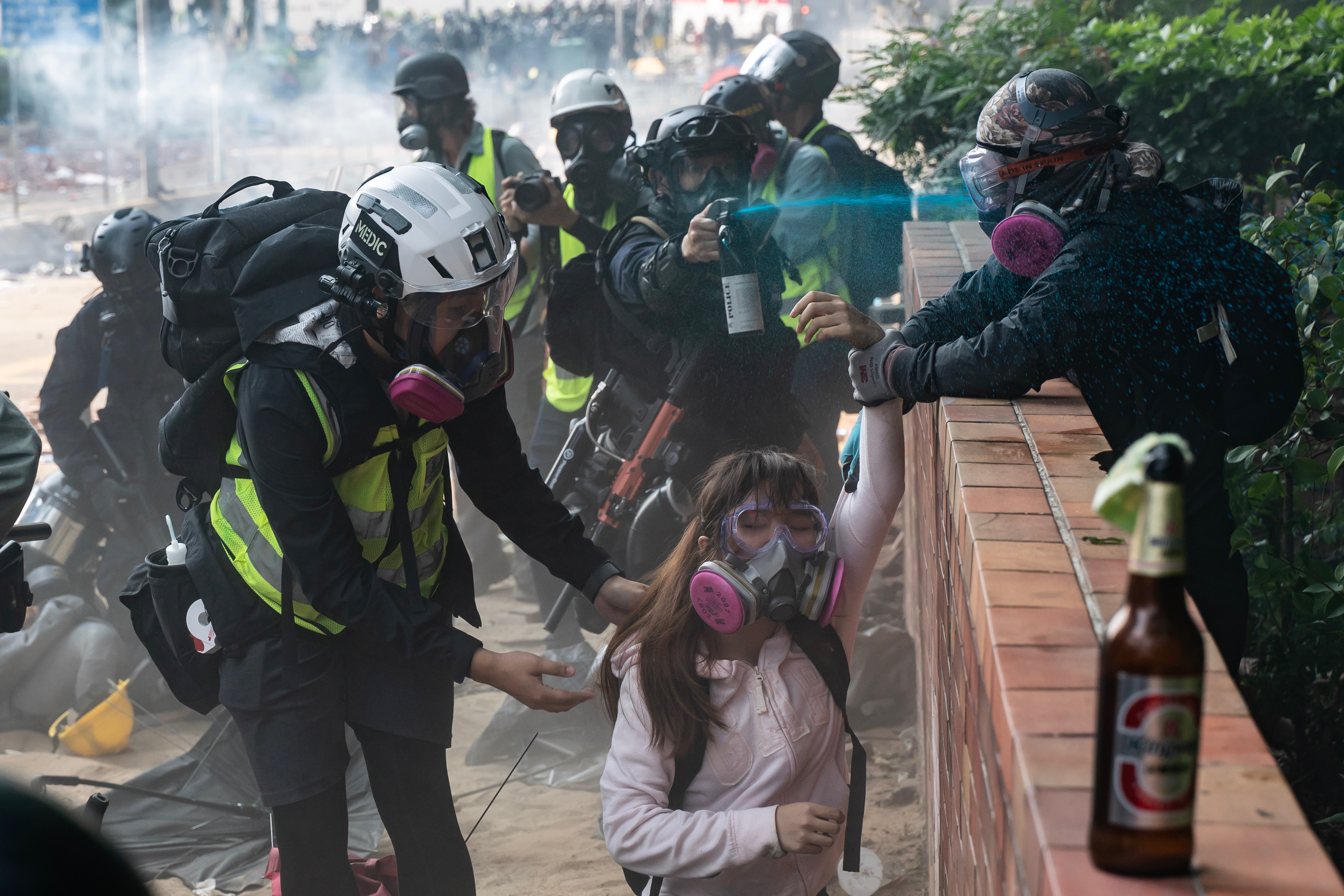 Police officer sprays protesters with identifying blue dye as they try to flee after occupying Hong Kong Polytechnic University campus on Monday