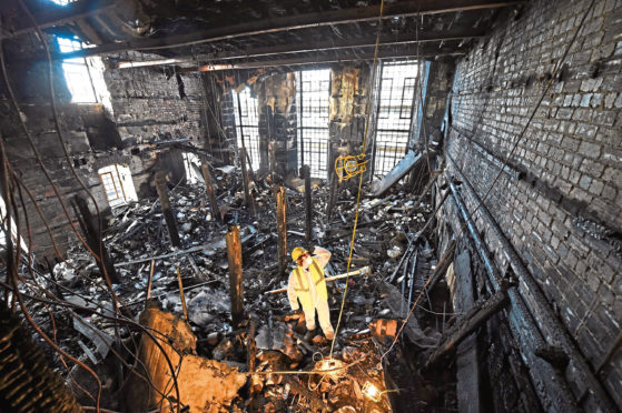 A forensic expert sifts through ashes of the art school library after 2014 fire