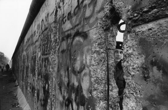 An East German soldier looks through the Berlin Wall in 1989