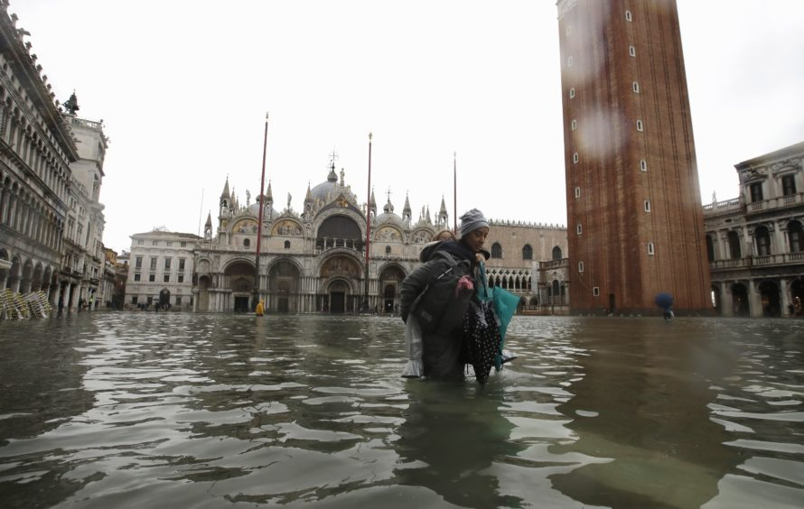 A woman carries her daughter in a flooded Piazza San Marco