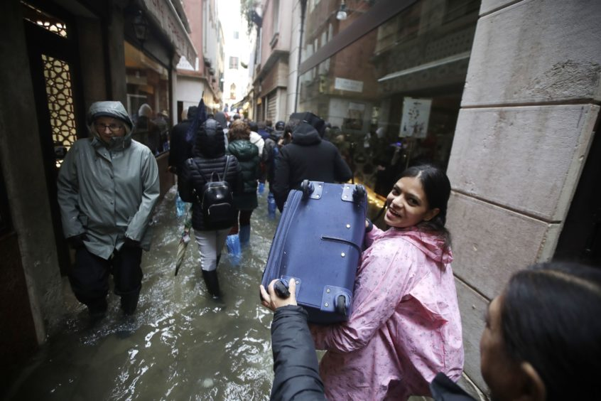 Tourists carry their luggage as they wade through water