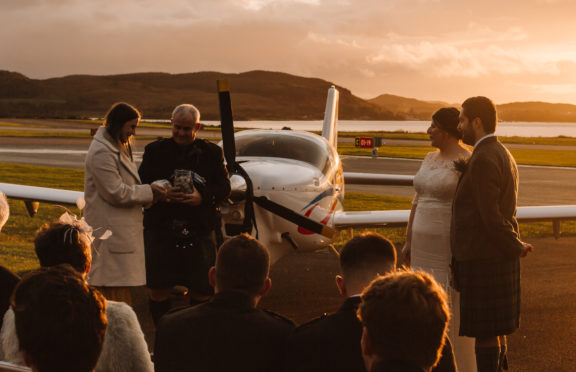 Groom's cousin, Sophie, and uncle, Mark, collect wishing stones as air traffic controller Lizzie Farrell                       and pilot Danny Fleming tie the knot at Oban Airport