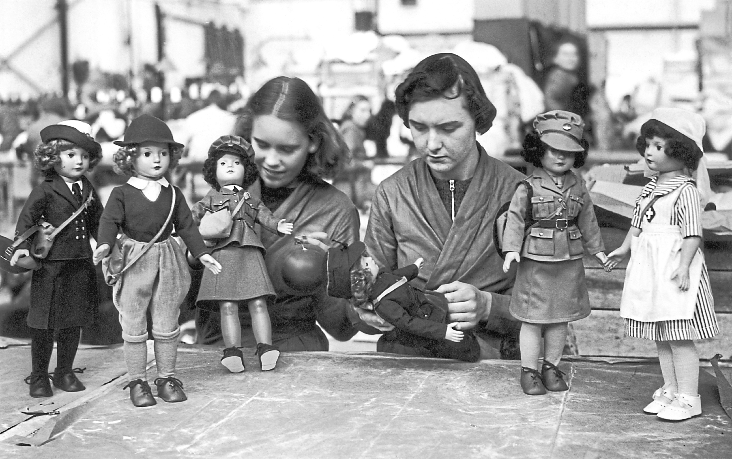 Workers in a British toy factory with dolls dressed in the uniforms of various women's war services, 19th October 1939. The toys are being produced in time for the first Christmas of the war.
