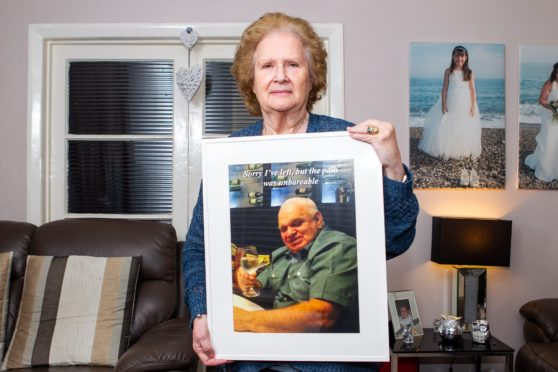 Catherine Scott with a photograph of her late husband David