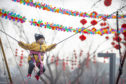 A child wearing a face mask on a ride at a fair in Longtan Park in Beijing yesterday