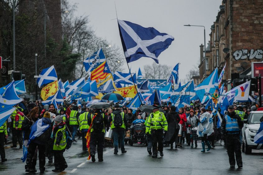 Marchers wave flags as they make their way towards the city centre