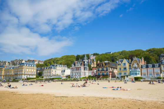 Sun worshippers relax on the beach in Trouville, north-west France