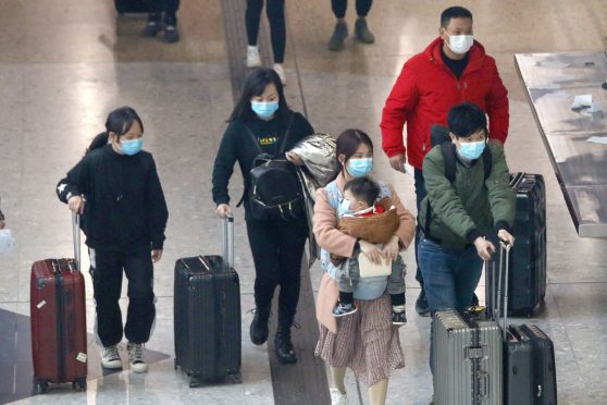 Travellers in Hong Kong wear masks