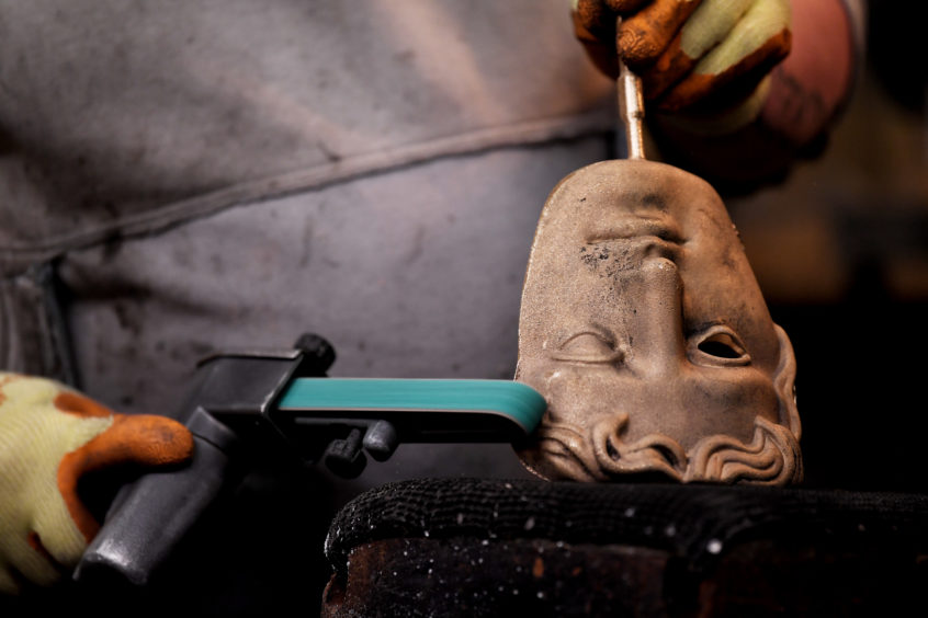 A BAFTA mask being polished