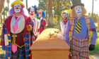 Cam (Eric Stonestreet, left) and fellow clowns take beloved mentor Al to his final resting place in TV series Modern Family