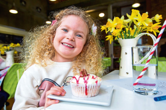 Wee Isabella has a big smile as she is about to enjoy a scrummy-looking cupcake at the Museum Of Rural life