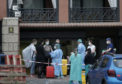 Health workers help guests leave the H10 Costa Adeje Palace hotel in Tenerife which has been under lockdown since an outbreak of coronavirus at the resort